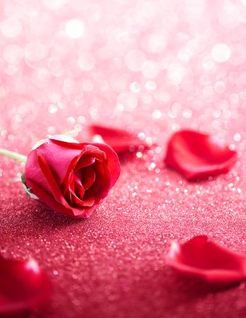 Photo pour Red rose and petal over glittering background - image libre de droit