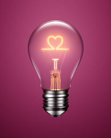 Foto de Light bulb with filament forming a heart icon on purple background - Imagen libre de derechos