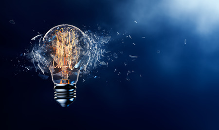 Photo pour Exploding light bulb on a blue background - image libre de droit