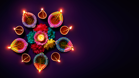 Foto de Colorful clay diya lamps with flowers on purple background - Imagen libre de derechos