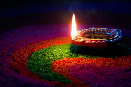 Photo for Happy Diwali - Diya lamp on top of colorful rangoli - Royalty Free Image