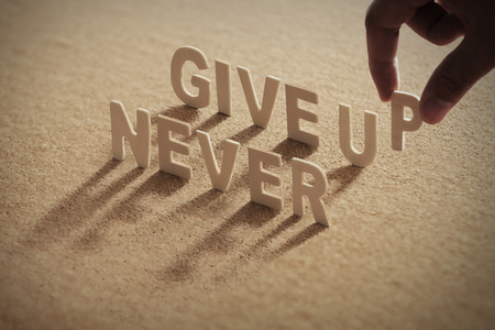 Photo pour NEVER GIVE UP wood word on compressed board with human's finger at P letter - image libre de droit