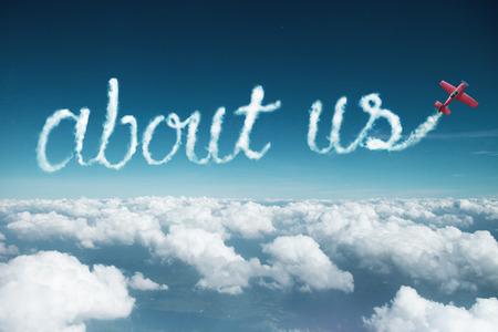 Foto de about us word created from a trail of smoke by Acrobatic plane. - Imagen libre de derechos