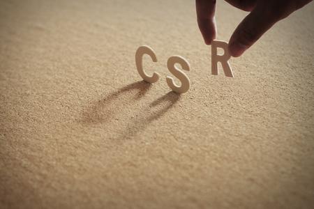 Foto de CSR wood word on compressed or corkboard with human's finger at R letter. - Imagen libre de derechos