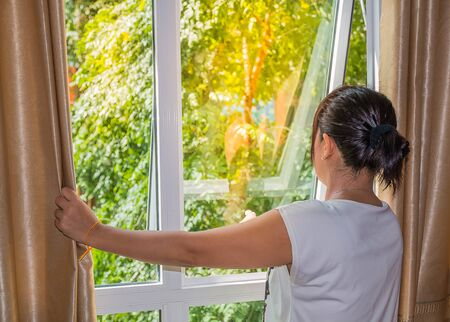 Photo for one lady open curtain at window - Royalty Free Image