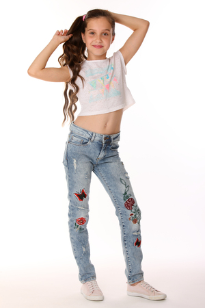 Photo pour Pretty beautiful happy brunette young teen girl in blue jeans and a bare belly. The adorable slender smiling preteen standing in sports shoes. The image of children's summer fashion. - image libre de droit
