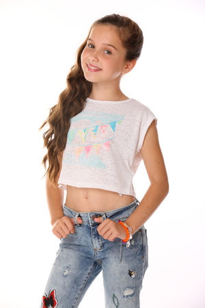 Photo for Portrait of beautiful happy brunette young teen girl in blue jeans and a bare belly. The adorable slender smiling preteen is an image of children's summer fashion. - Royalty Free Image