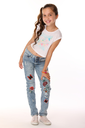 Photo for Pretty beautiful happy brunette young teen girl in blue jeans and a bare belly. The adorable slender smiling preteen standing in sports shoes. The image of children's summer fashion. - Royalty Free Image
