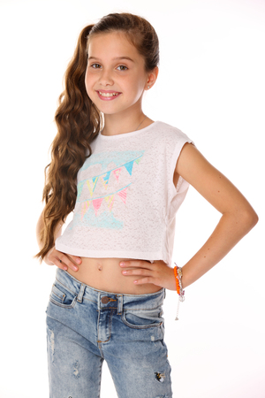 Photo pour Portrait of beautiful happy brunette young teen girl in blue jeans and a bare belly. The adorable slender smiling preteen is an image of children's summer fashion. - image libre de droit