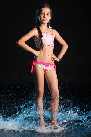 Photo for Adorable young teenage girl in a swimsuit stands barefoot in splashing water. Pretty child with dark hair, beautiful face and a slim figure. Slender preteen in a bikini. - Royalty Free Image