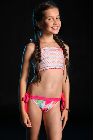Photo pour Portrait of a happy young teenage girl in a swimsuit. Pretty child with dark hair and beautiful face adorably smiles. Slender preteen in a bikini. - image libre de droit
