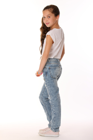 Photo for Pretty beautiful brunette young teen girl in blue jeans. The adorable slender preteen standing on a white background in sports shoes. The image of children's summer fashion. - Royalty Free Image