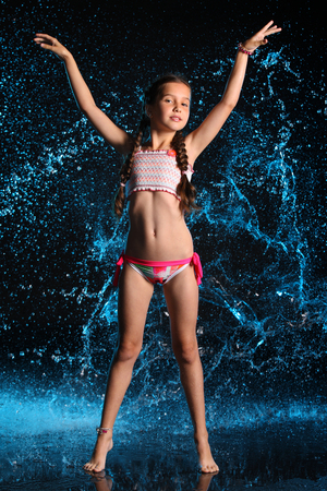 Photo pour Adorable young teenage girl in a swimsuit stands barefoot in splashing water. Pretty child with dark hair, beautiful face and a slim figure. Slender preteen in a bikini. - image libre de droit