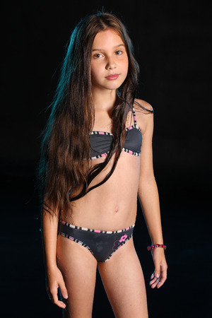 Photo pour Attractive pretty young teenage girl posing in a wet bikini. The child with long chic dark hair and a beautiful slender body. Lovely pre-teen female stands in swimsuit. - image libre de droit