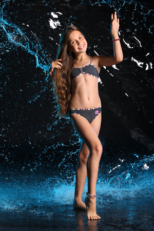 Photo pour Attractive happy young teenage girl posing in a dark bikini. The child with long chic hair and a beautiful slender body smiles charmingly. Lovely pre-teen female dances barefoot in swimsuit. - image libre de droit