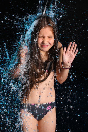 Photo pour Conceptual photo: negative, stress, trouble, fright. The water flow falls on a gentle little slender child girl in a bikini. Young female teenager in a falling stream of water. - image libre de droit
