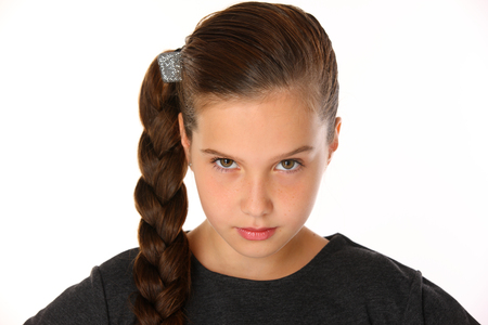 Photo pour Close-up portrait of pretty slender young schoolgirl in uniform. Beautiful attractive little girl posing in business clothes. Cute child is serious and demanding. - image libre de droit