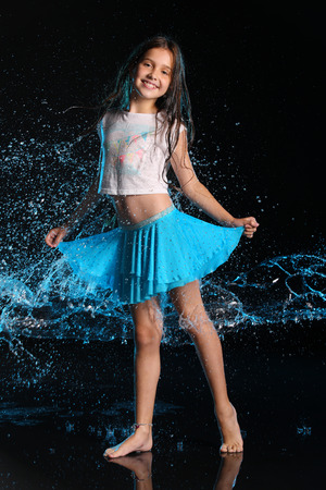 Foto de Charming slender child standing at full body and smile. Pretty young beautiful girl with bare legs in wet clothes and skirt. Attractive happy teenager in splashes of water. - Imagen libre de derechos