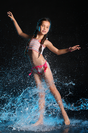 Photo pour Charming slender child standing at full body on tiptoe. Pretty young beautiful girl with bare legs elegantly posing in wet bright bikini. Attractive young teenager in splashes of water. - image libre de droit