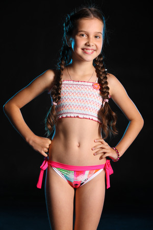 Photo pour Portrait of a charming child standing with slender body. Pretty young beautiful girl with bare belly posing in bright bikini. Attractive young teenager smiling and happy. - image libre de droit