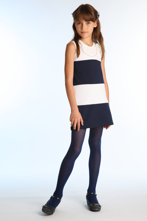 Foto de Beautiful girl in a striped dress is standing at full length. Elegant attractive child with a slender body and long legs in blue tights. The young schoolgirl is 9 years old. - Imagen libre de derechos