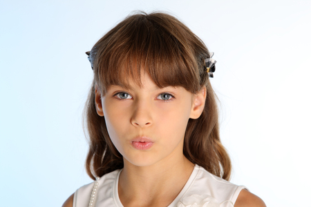 Photo pour Close-up portrait of a beautiful girl in a white blouse. The cute attractive playful child teases by pulling her mouth. The young schoolgirl is 9 years old. - image libre de droit
