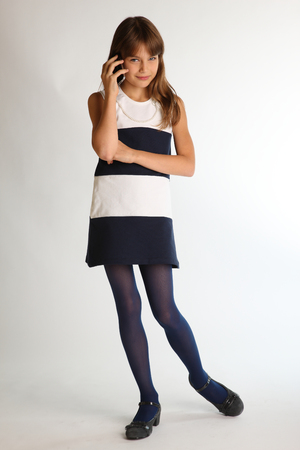 Foto de Beautiful girl in a striped dress is standing at full length with a smartphone and smiling. Attractive child with a slender body and long legs in blue tights. The young schoolgirl is 9 years old. - Imagen libre de derechos
