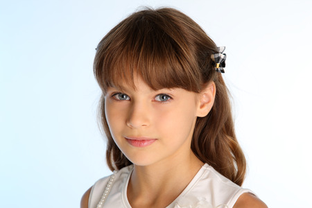 Photo pour Close-up portrait of a beautiful girl in a white blouse. Pretty attractive child. The young schoolgirl is 9 years old. - image libre de droit