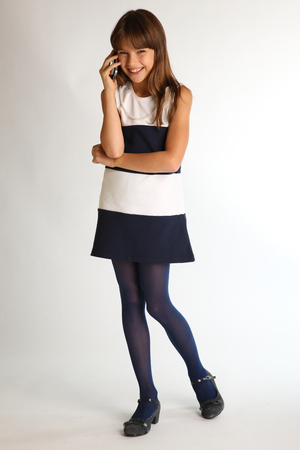 Foto de Beautiful girl in a striped dress is standing at full length with a smartphone and laughing. Elegant attractive child with a slender body and long legs in blue tights. Young schoolgirl 9 years old. - Imagen libre de derechos