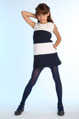 Photo pour Beautiful girl in a striped dress is standing at full length. Elegant attractive child with a slender body and long legs in blue tights. The young schoolgirl is 9 years old. - image libre de droit