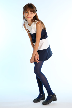 Foto de Beautiful girl in a striped dress is standing at full length and smiling. Elegant attractive child with a slender body and long legs in blue tights. The young schoolgirl is 9 years old. - Imagen libre de derechos
