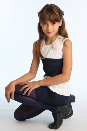 Foto de Slender beautiful girl in a striped dress sat on her knee. Pretty happy attractive child in blue tights. The young schoolgirl is 9 years old. - Imagen libre de derechos