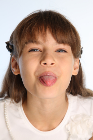 Photo pour Close-up portrait of a beautiful girl in a white blouse. Cute attractive child teases and shows her pink tongue. The young schoolgirl is 9 years old. - image libre de droit