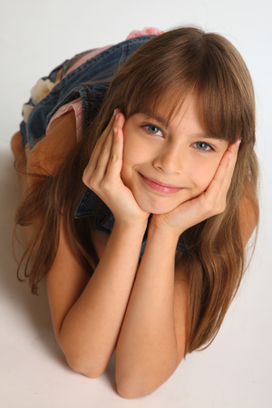 Photo for Portrait of a beautiful girl in a denim shorts is resting on the floor. Pretty attractive child with a lovely smiling face. The young schoolgirl is 9 years old. - Royalty Free Image