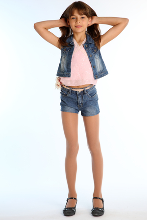 Photo pour Beautiful girl in a denim shorts is standing at full length. Elegant attractive child with a slender body and long legs in pantyhose. The young schoolgirl is 9 years old. - image libre de droit