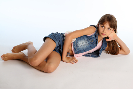 Photo for Beautiful girl in a denim shorts is resting on the floor barefoot. Elegant attractive child with a slender body and bare long legs. The young schoolgirl is 9 years old. - Royalty Free Image