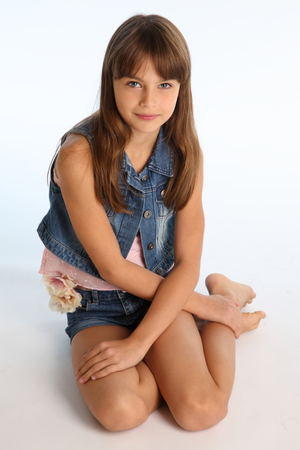 Photo pour Beautiful girl in a denim shorts is resting on the floor barefoot. Elegant attractive child with a slender body and bare long legs. The young schoolgirl is 9 years old. - image libre de droit