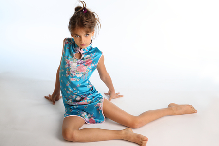 Foto de Beautiful girl in an asian blue dress is sitting barefoot. Elegant attractive child with a slender body and bare long legs. The young model 9 years old in fashion style. - Imagen libre de derechos