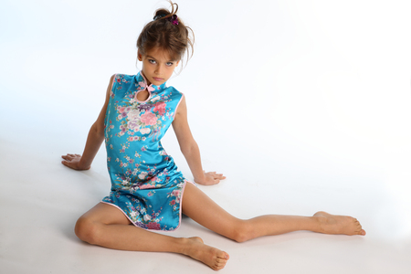 Photo pour Beautiful girl in an asian blue dress is sitting barefoot. Elegant attractive child with a slender body and bare long legs. The young model 9 years old in fashion style. - image libre de droit