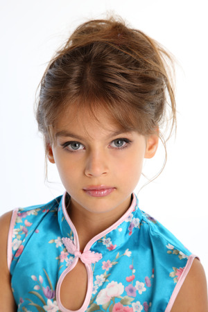 Foto de Close-up portrait of a beautiful girl in an asian blue dress. The young attractive child 9 years old in fashion style. - Imagen libre de derechos