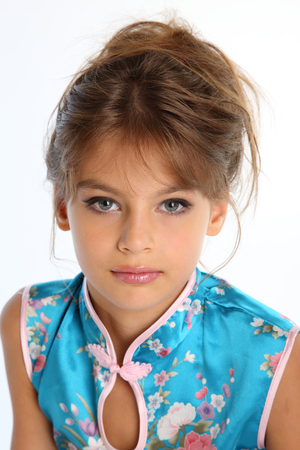 Photo pour Close-up portrait of a beautiful girl in an asian blue dress. The young attractive child 9 years old in fashion style. - image libre de droit
