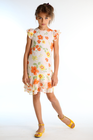 Photo pour Tanned little girl in a bright summer dress is standing on white background. Attractive child with a slender body and long bare legs in yellow shoes. The young model 9 years old in fashion style. - image libre de droit