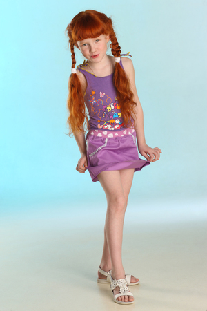 Photo for Beautiful charming little redhead girl shows her summer clothes at full length. Happy attractive child with a slender body and slim bare legs. The young pre-teen girl 8 years old. - Royalty Free Image