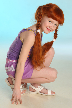 Photo for Beautiful charming little redhead girl demonstrates her summer clothes squatting. Happy attractive child with a slender body and slim bare legs. Fashion pre-teen model 8 years old. - Royalty Free Image