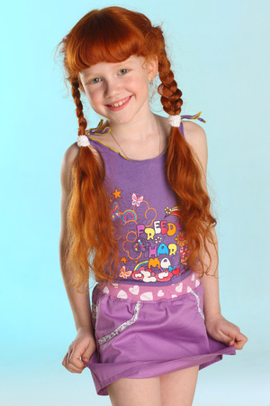 Photo pour Portrait of beautiful charming little redhead girl. She shows her summer clothes. Happy attractive child with a slender body and slim bare legs. The young pre-teen model 8 years old. - image libre de droit