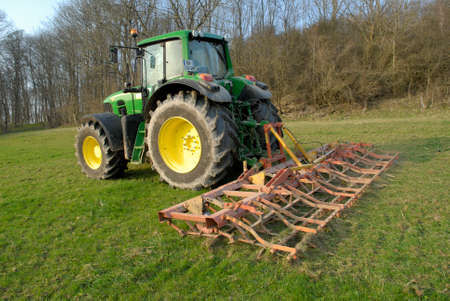 Photo for Normandy, France, March 2012. Soil is worked with surface tools. Farmer preparing his meadow using a harrow. - Royalty Free Image