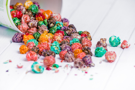 Foto de Brightly Colored Candied Popcorn, white background. Horizontal image of Junk food, fruit flavored popcorn in light pink bowl. Colorful, rainbow, candy coated popcorn. Shallow focus on popcorn in bowl - Imagen libre de derechos