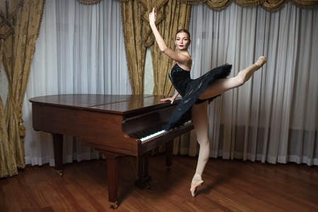 Ballerina in black tutu standing on pointes at the grand piano