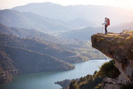 Photo pour Female hiker standing on cliff and enjoying valley view - image libre de droit