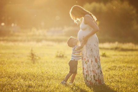 Photo pour Small boy kissing belly of his pregnant mother outdoors - image libre de droit